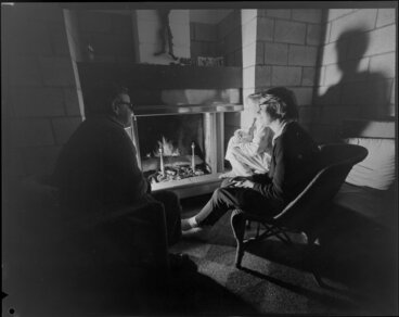 Image: People sitting at open fire, living room, Jim Beard's house, Waikanae, Kapiti Coast
