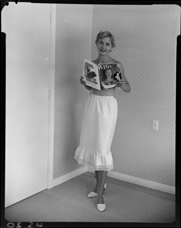 Image: Topless woman in half slip reading 'Wife' magazine