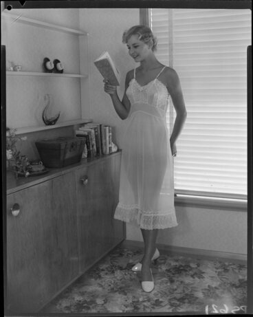 Image: Woman in slip, reading 'The Snow Goose'