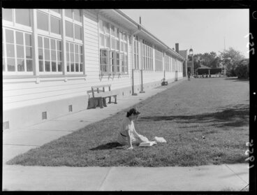 Image: Young girl, reading on the grass in front of a school, during a water shortage, Marton, Rangitikei District