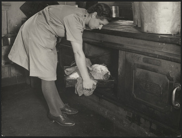 Image: Cook from the Women's Army Auxiliary Corps putting meat in an oven to roast, for men at a World War II military camp in New Zealand