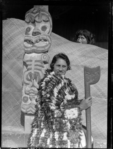 Image: Tarihira Mihinui dressed in a feather cloak holding a tewhatewha, sitting by a carved wooden pou, Otūkou marae, Lake Rotoaira