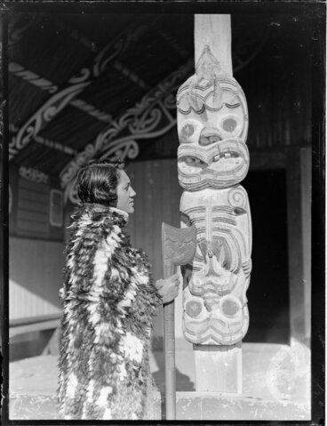Image: Tarihira Mihinui dressed in a feather cloak holding a tewhatewha, next to a carved wooden pou, Otūkou marae