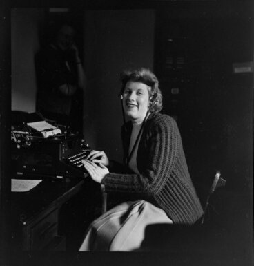 Image: Qantas employee Miss Cullen (Publicity Manager's Office) at typewriter wearing headphones [Qantas headquarters, Mascot, New South Wales?] Australia