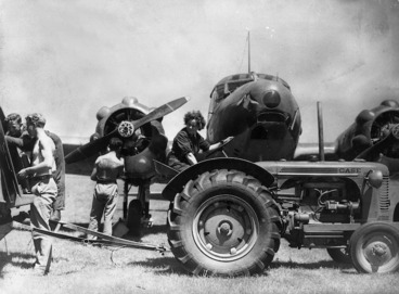 Image: Woman driving a tractor alongside a Avro Anson training plane, during World War II