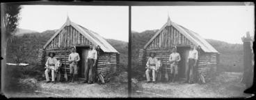 Image: Men, including photographer William Williams (left), outside log cabin set in bush, Southland Region [Fiordland?], including canoe paddles and guns