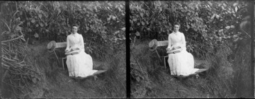 Image: Lydia Myrtle Williams reading book on bench in garden, location unidentified
