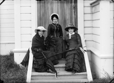 Image: The Devereux sisters, Margaret Ellen (Nellie), Lydia Myrtle, and Marian Amy, on the back steps of their family home, Lower Hutt, Wellington Region