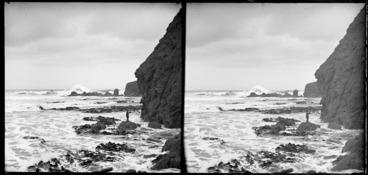 Image: Stormy coastal scene, featuring kelp and cliffs, and including an unidentified boy standing on a rock, Black Head, Dunedin, Otago Region