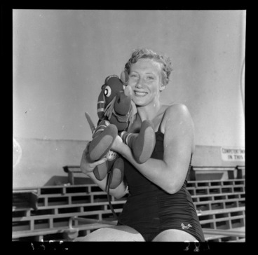 Image: [Swimmer?] Marion Roe sitting in her swimsuit at the poolside holding a stuffed toy elephant