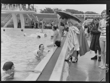 Image: An unidentified woman, sheltering under an umbrella and talking to swimmers, Naenae Olympic Swimming Pool, Lower Hutt