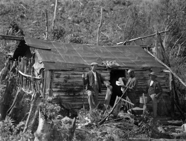 Image: A scrubland scene showing a hut with three men standing outside