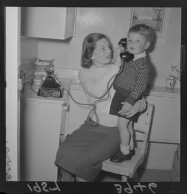 Image: Unidentified young boy and his mother with a new telephone in their kitchen, Wellington