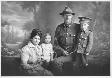 Image: 3/4 group portrait showing Sergeant Francis and family, boy on the right wears a child's military uniform and his father's 4th (Waikato) Mounted Rifles hat.