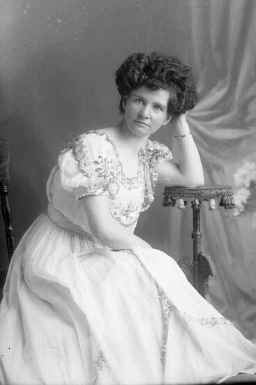 Image: 3/4 portrait of Miss Nicholson seated leaning her left elbow on....