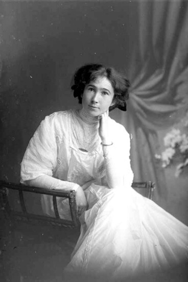 Image: 3/4 portrait of Miss Robinson seated, leaning her left elbow on....