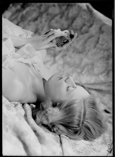 Image: 1/4 length portrait of a model lying down holding a cosmetic bottle, for Sargood Son and Ewen 1940
