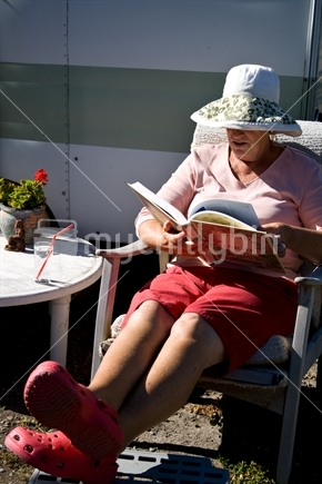 Image: Woman relaxes outdoors with a book