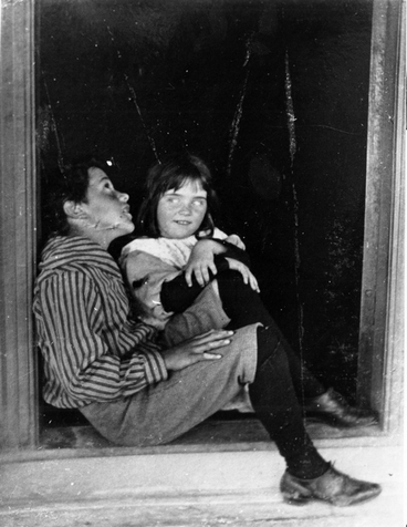 Image: A boy and a girl sitting in a doorway
