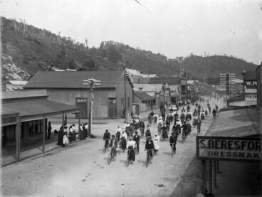 Image: Cyclists in a Greymouth street, passing the premises of Mrs S Beresford, dressmaker, between 1898 and 1905