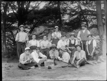 Image: A group portrait of the summer campers, showing some playing cards, one holding a tomahawk, one holding an axe, one holding a mallet, two holding brooms and one pouring beer into a glass and two smoking, probably Christchurch district