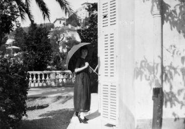 Image: Katherine Mansfield standing with a parasol by the Villa Isola Bella, France
