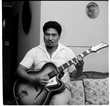 Image: Henare Gilbert singing and playing his guitar at his home in Stokes Valley