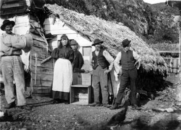 Image: People standing outside a whare in Plimmerton