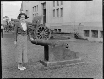Image: Unidentified young woman standing beside military cannon [outside a museum? Christchurch?]