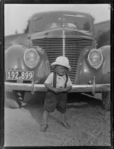 Image: Young Māori boy crying in front of a vehicle