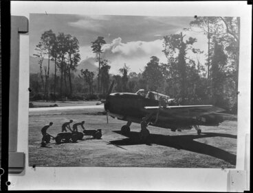 Image: Men loading bombs onto a Grumman Avenger on Bougainville Island