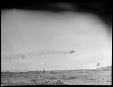 Image: Farmland at Ihumatao, Mangere, Manukau City, Auckland Region, featuring an aerial topdressing plane [ZK-ANN Tiger Moth?] in action, with onlookers standing in the paddock