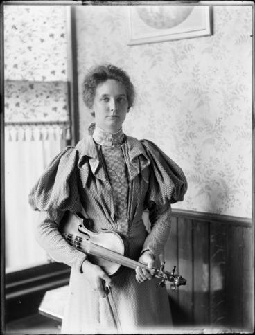 Image: Nellie Devereux holding [viola? violin?], location unknown