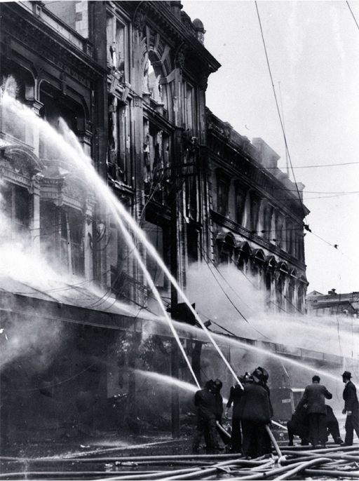 Firemen dampening down the main entrance of Ballantyne's, Colombo Street, Christchurch
