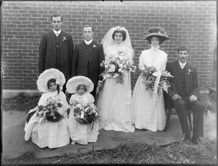 Wedding party portrait on long grass in front of brick wall, unidentified bride with long veil and groom, bridesmaid with large hat, best men and flower girls with large bonnets, probably Christchurch region