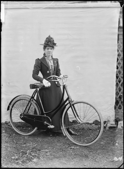 Unidentified young woman, with a bicycle, outdoors, with a backdrop, probably Christchurch district