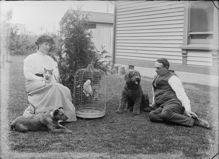 Unidentified man and woman with domestic pets, including two dogs, a cat, and a bird in a cage, sitting on a grass lawn outside a wooden building, possibly Christchurch district
