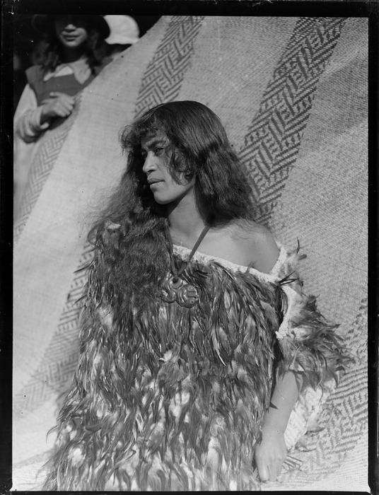 Annie Ngauru Hoko (nee Downs) standing by a whariki flax mat with woven design, Tokaanu