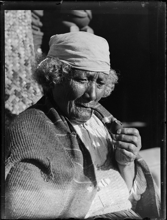 Portrait of an unidentified elderly Maori woman with a moko, bandana and pipe, sitting in front of a meeting house, probably Taupo