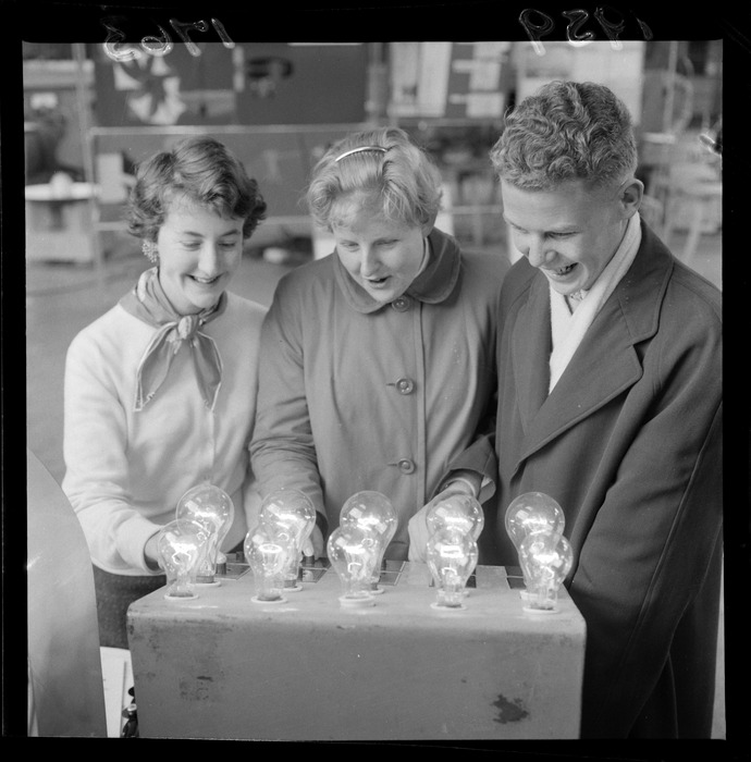 Group of unidentified young people, looking at an object with lightbulbs on it [at a science fair?]