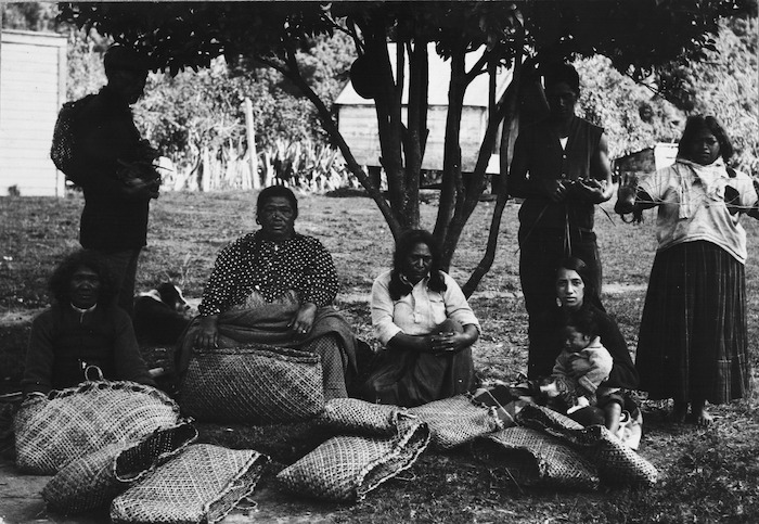 Group of men and women with kete and other items made from flax