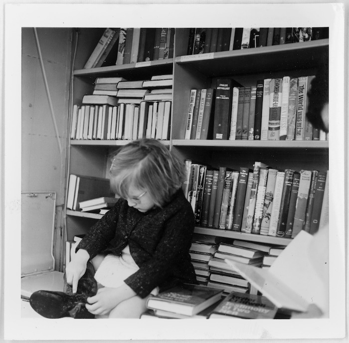 Child photographed against shelves of books