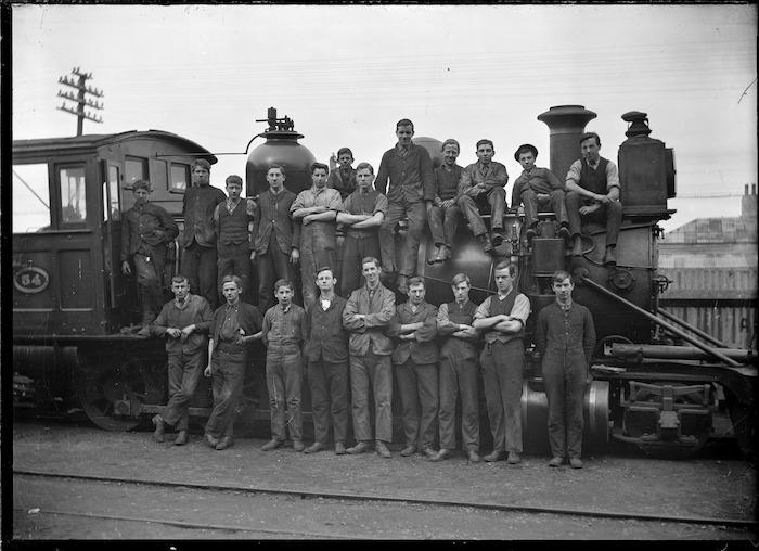 O Class steam locomotive NZR 54, 2-8-0 type, with a group of men on and beside the engine.