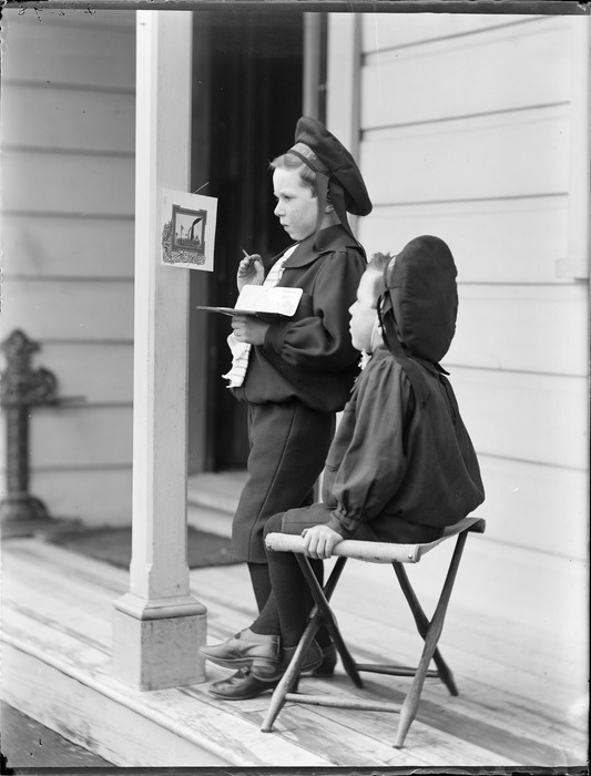 Edgar and Owen, on the porch of their house; Edgar is painting a picture hanging on the pillar, Royal Terrace, Kew, Dunedin