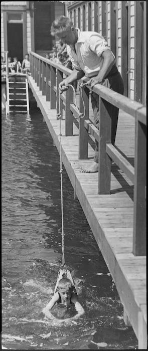 Assistant at Te Aro Baths, Wellington, teaching a boy to swim