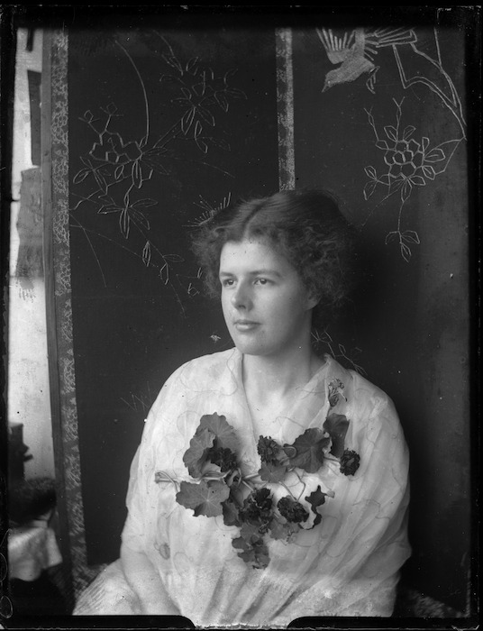 Woman seated in front of a decorative screen