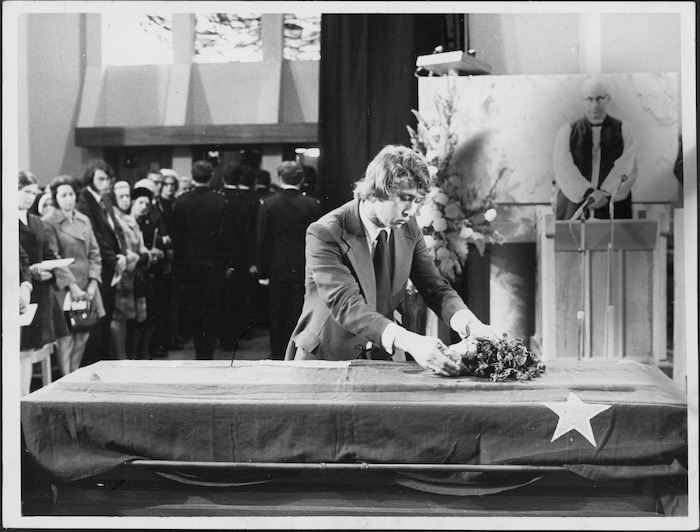 John Kirk placing flowers on his father's casket during the state funeral of Prime Minister Norman Kirk at St Paul's Cathedral, Wellington