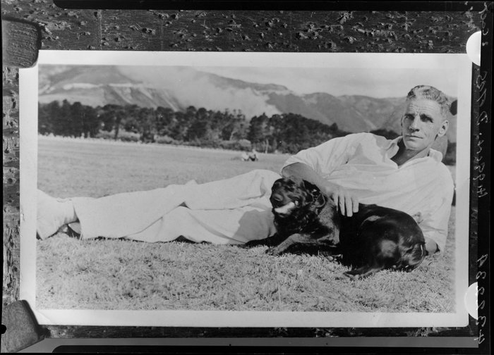 Unidentified man with dog, in countryside