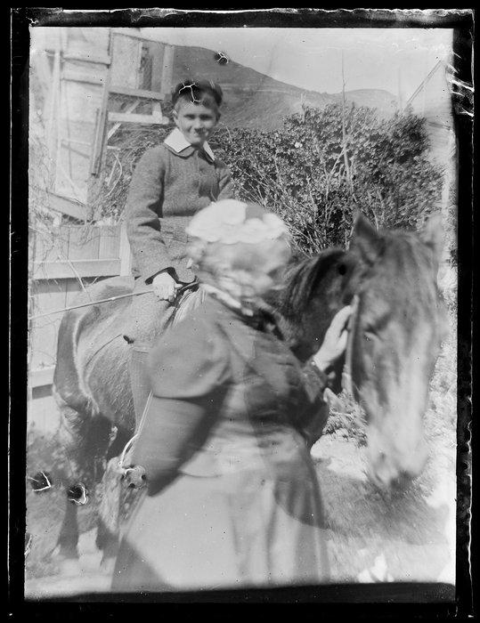 Sarah Jane Kirk standing beside a boy on a horse