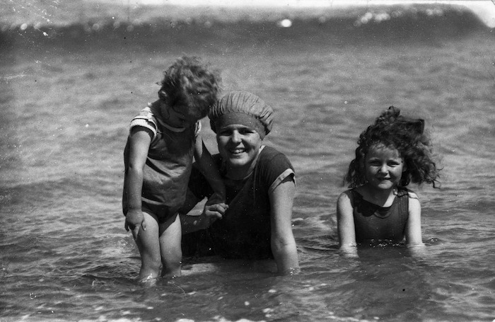 A women and two children, wearing swimming costumes in the sea